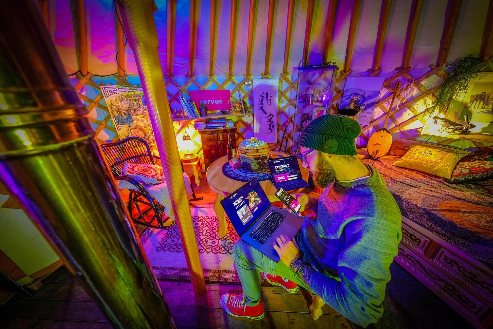 Rowan Hartsuiker working on a laptop inside his yurt studio