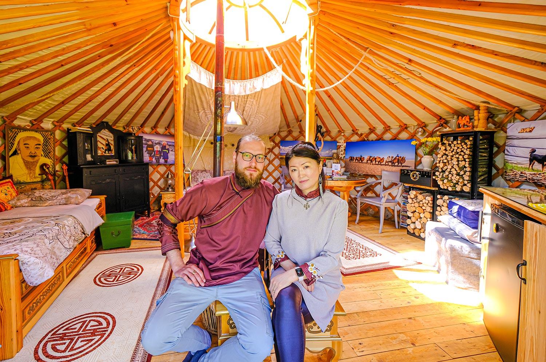 Rowan with his wife posing inside a yurt