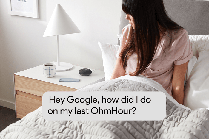 A woman in bed looking at her Google Home Mini on the night stand