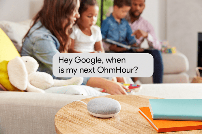 Google Home Mini shown in a living room with a family of four playing games