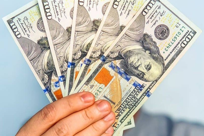 a hand holding 100 dollar bills showing that you can save money with the Smart Power program