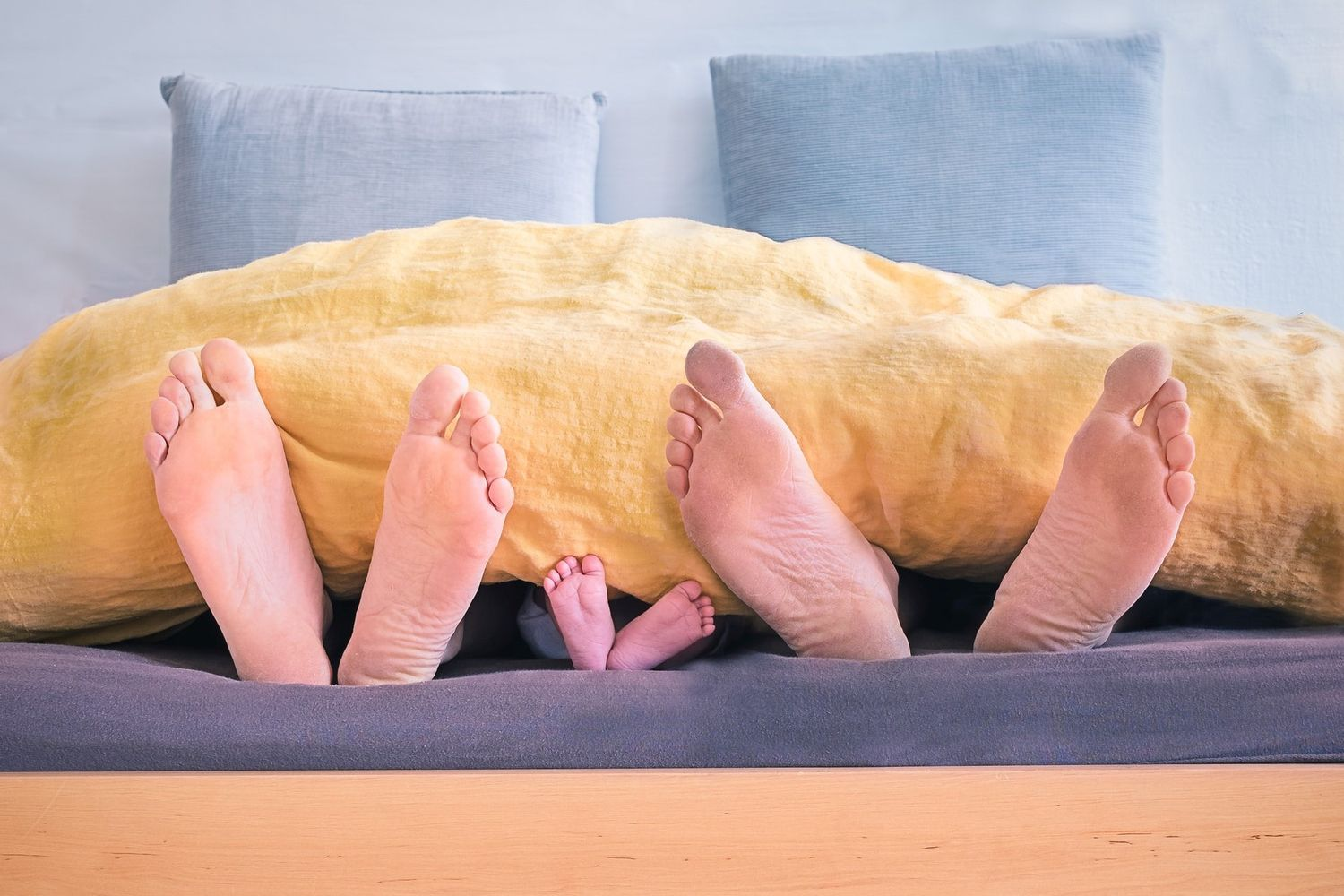 feet of a family under the blanket in a bed participating in autoohm without lifting a finger