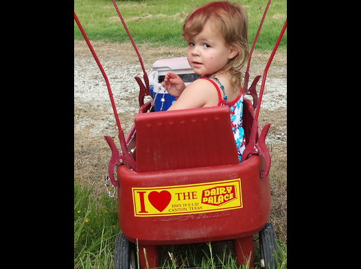 Photo of a girl in a radio flyer wagon with a DP bumper sticker stuck to it