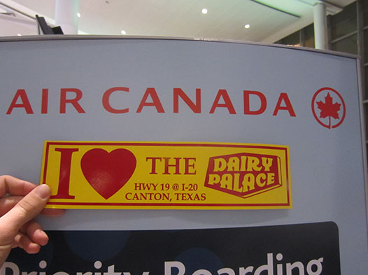 Photo of  someone holding a DP bumper sticker up in an airport in Canada