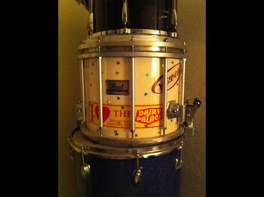 Photo of a drum set with a DP bumper sticker stuck to one of the drums