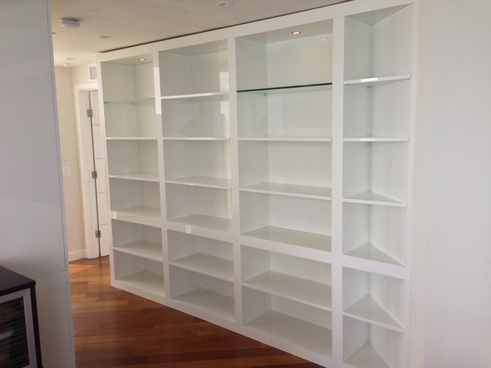 High Gloss White Acrylic Bookshelf with Pivoting Section That Hides Bedroom