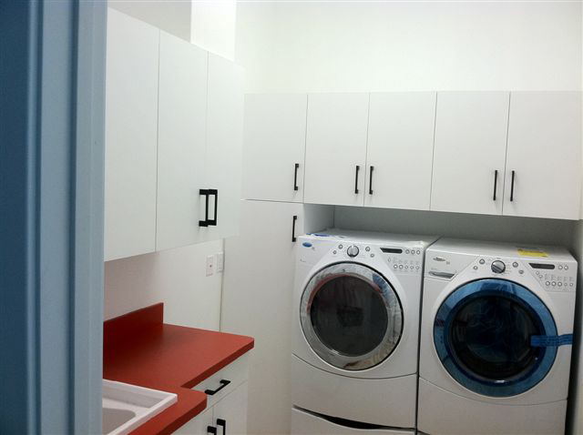White Laundry Room With Red Counters