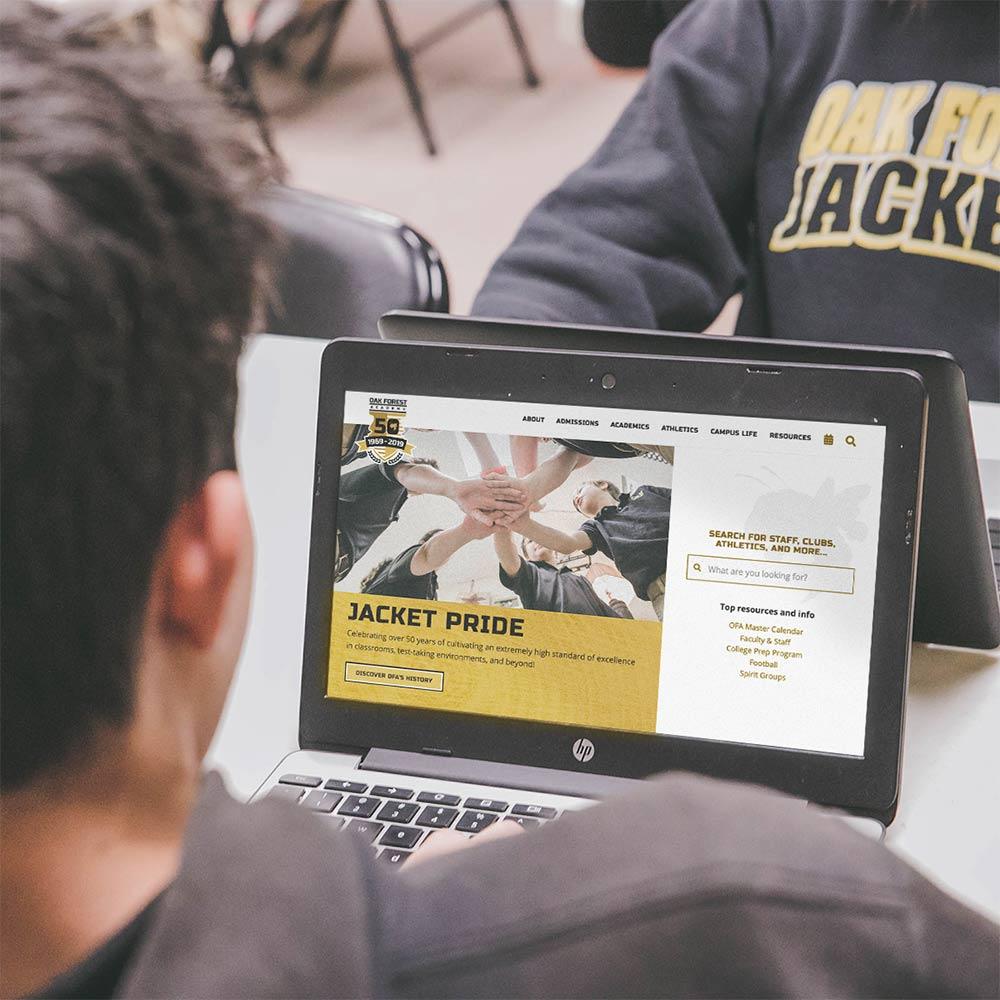 Oak Forest Academy student on laptop showing ofajackets.org