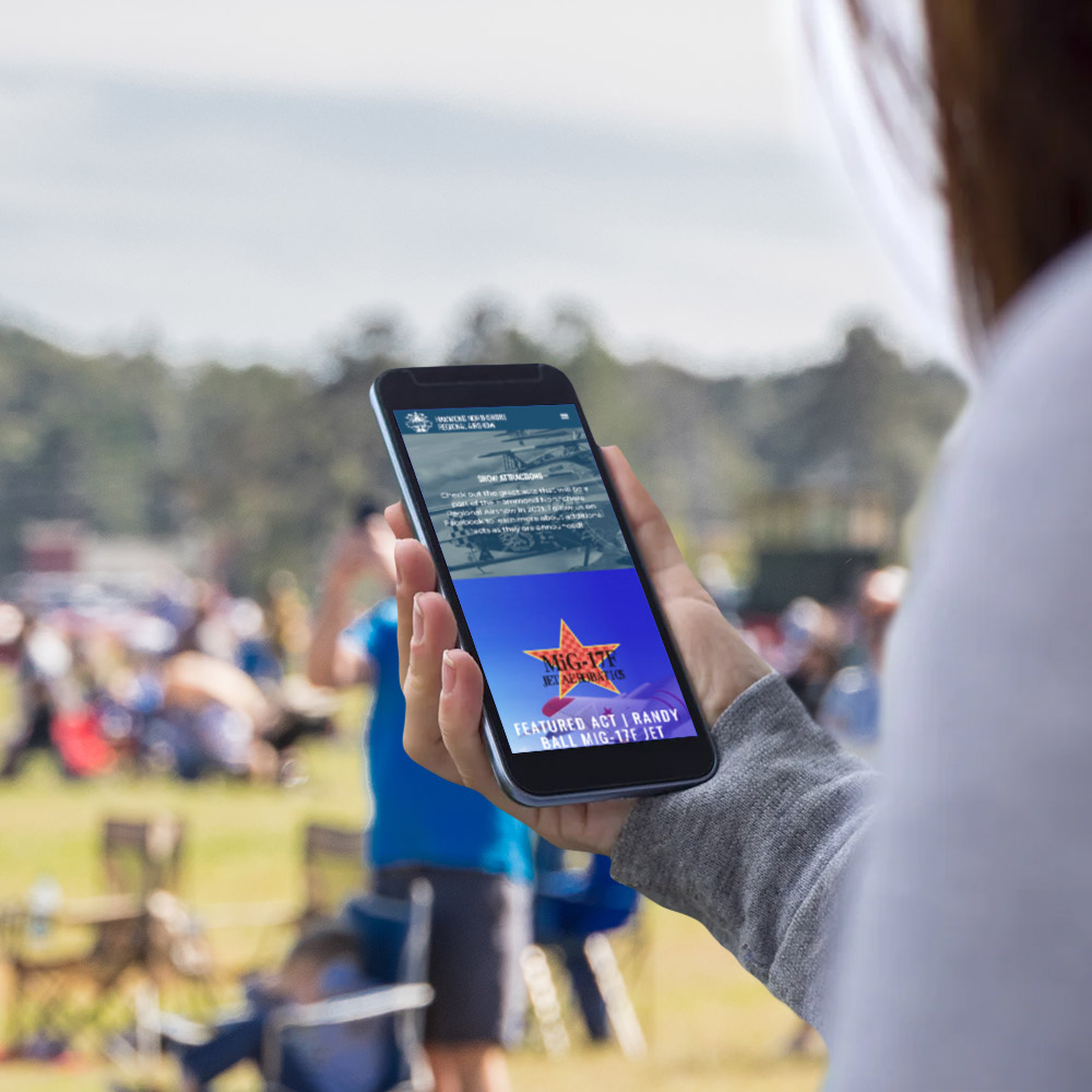 Young woman looking at the upcoming attractions for the Hammond Northshore Regional Airshow on here smartphone.
