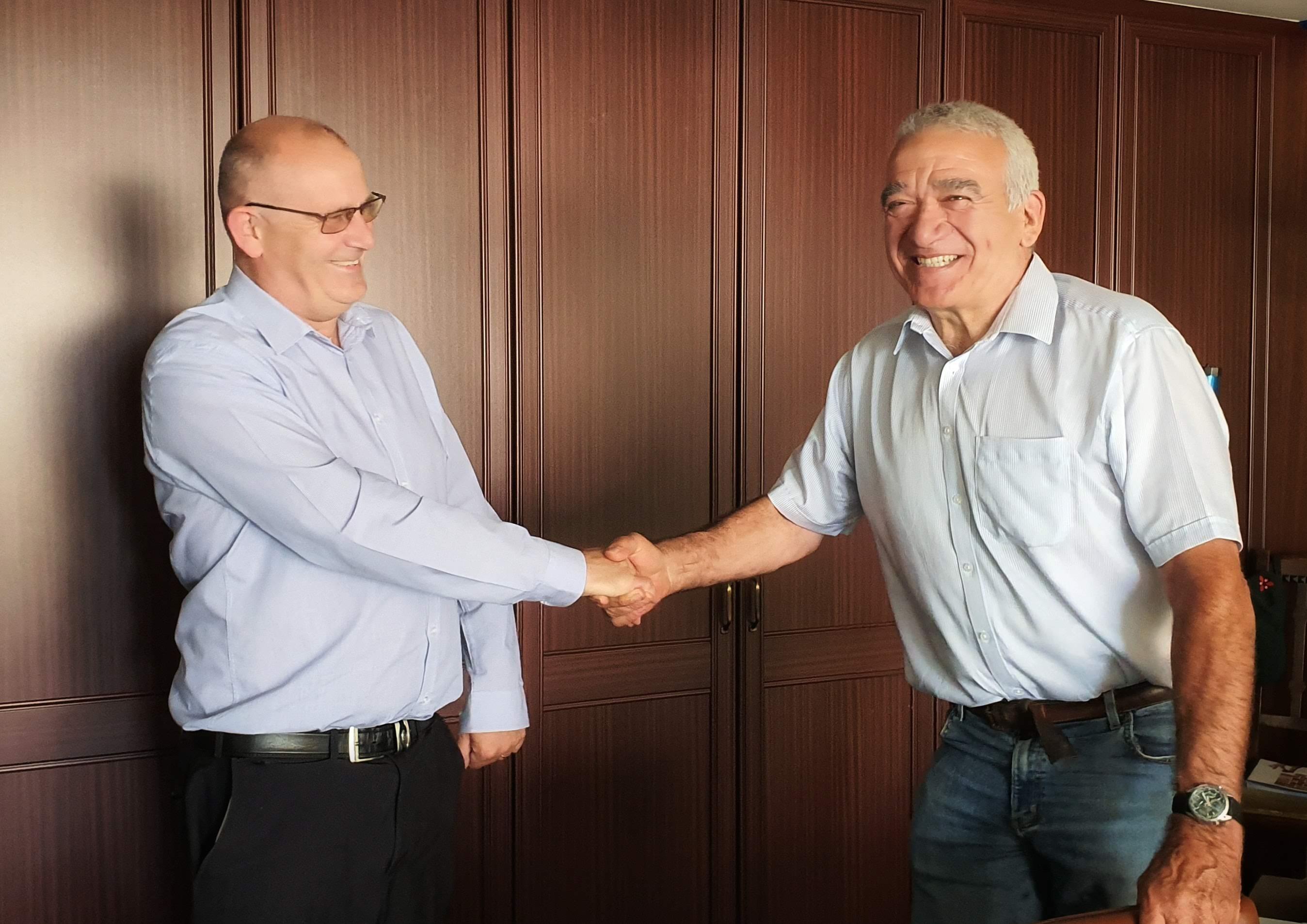 Richard Greetham congratulated by Robert Oldershaw for his long service award