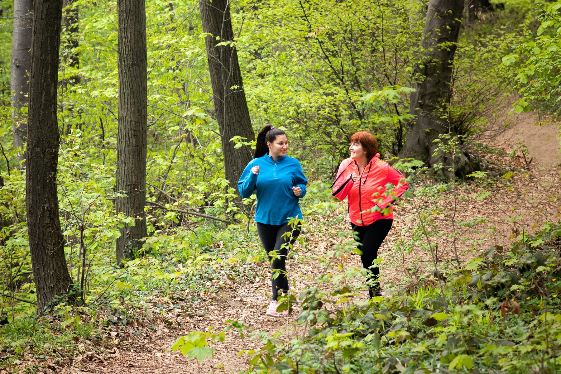 Two women jogging through woods