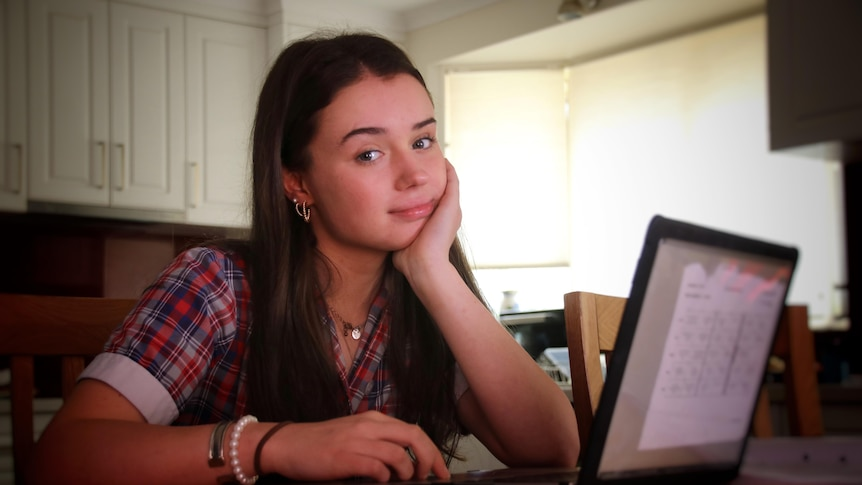 A teenage girl sitting at her laptop in her school uniform at the kitchen table.