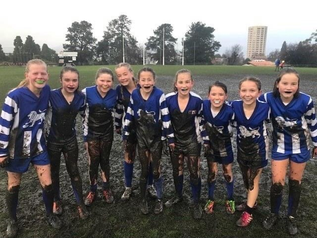 Nine young girls wearing muddy blue and white football jerseys smiling on a football field.