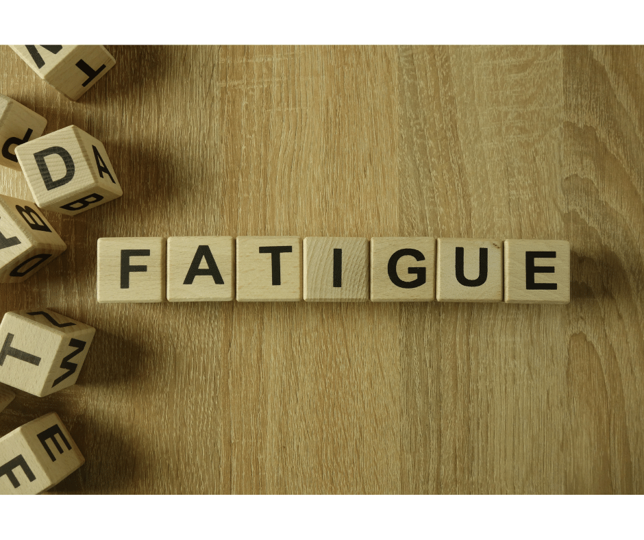 Image is a photograph of wooden blocks with letters printed on them. The blocks spell the word Fatigue.