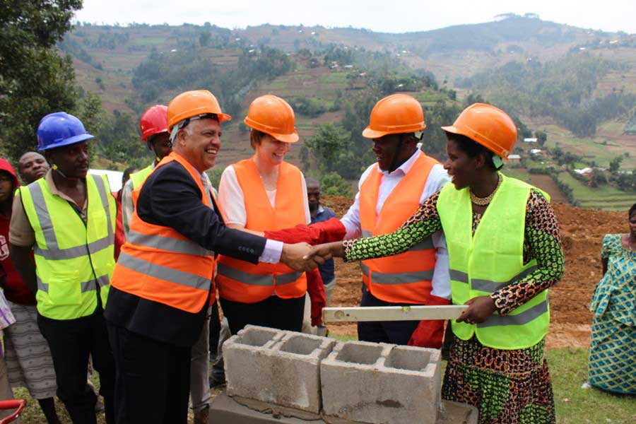 (left to right) Dr. Alex Coutinho, Ophelia Dahl, Burera Mayor Florence Nambajemariya, and Northern Province Governor Jean Marie Vianney Gatabazi, lay the first bricks of the construction of the Butaro Cancer Patient Support Center in Rwanda.