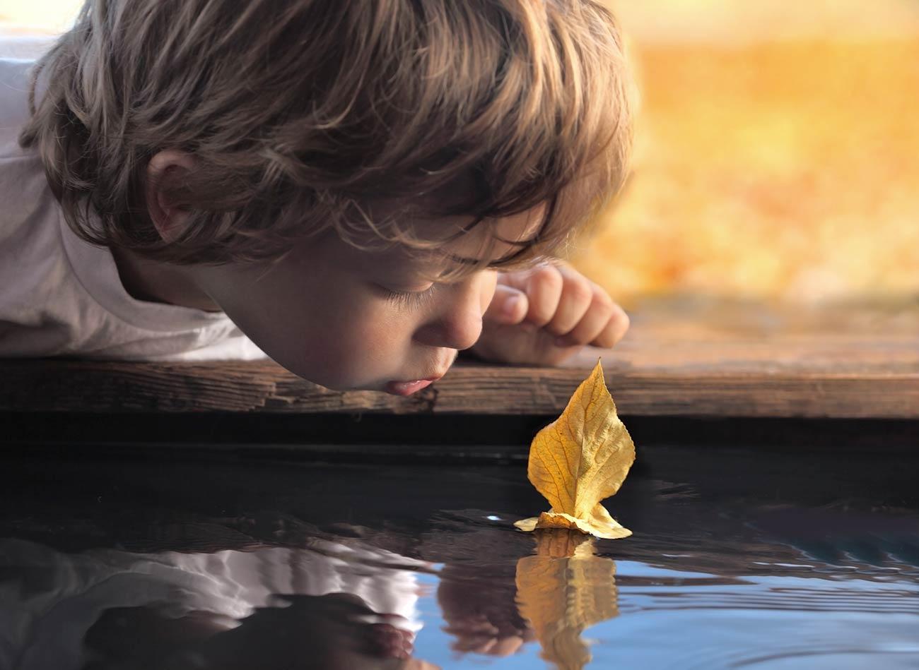 Bild - Kleiner Junge pustet ein Blatt auf dem Wasser