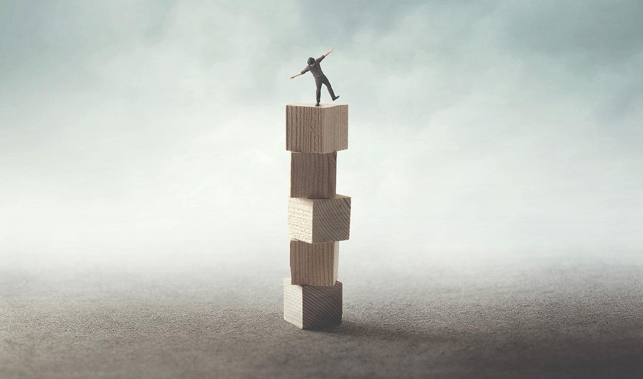 Bild –Illustration mit Bauklötzen auf dem ein kleiner Mann steht, der darauf balanciert.