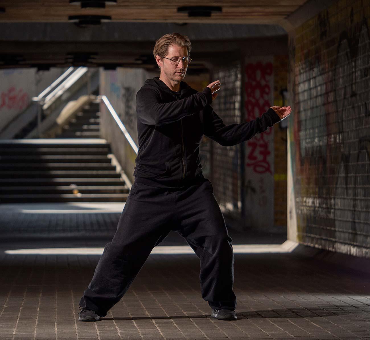 Bild –Toby O. Rink beim Taiji üben in einer Unterführung. An den Wänden Graffitis.
