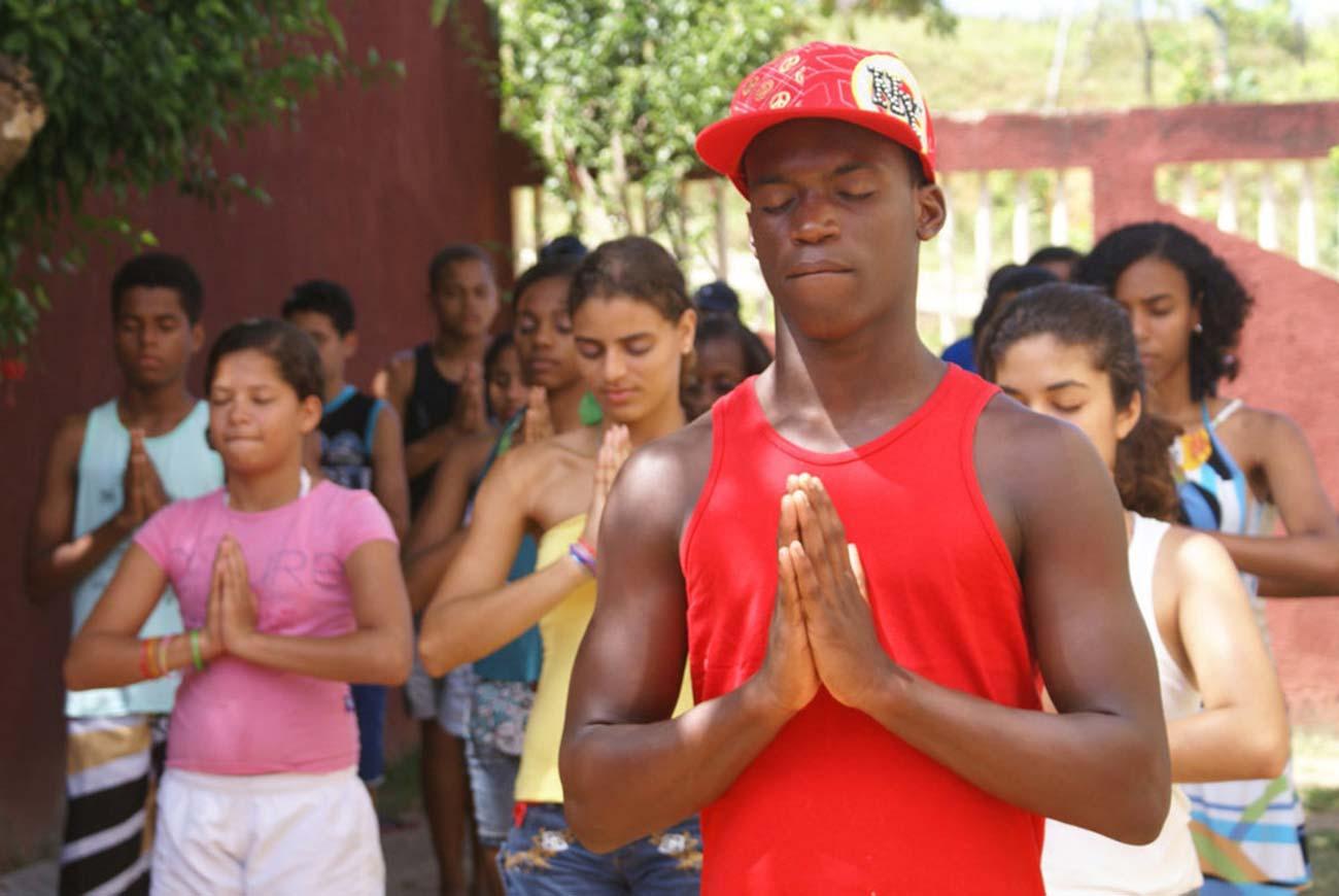 Bild –Ein Gruppe Jugendlicher, die stehend beide Hände vor der Brust halten und die Augen geschlossen haben.