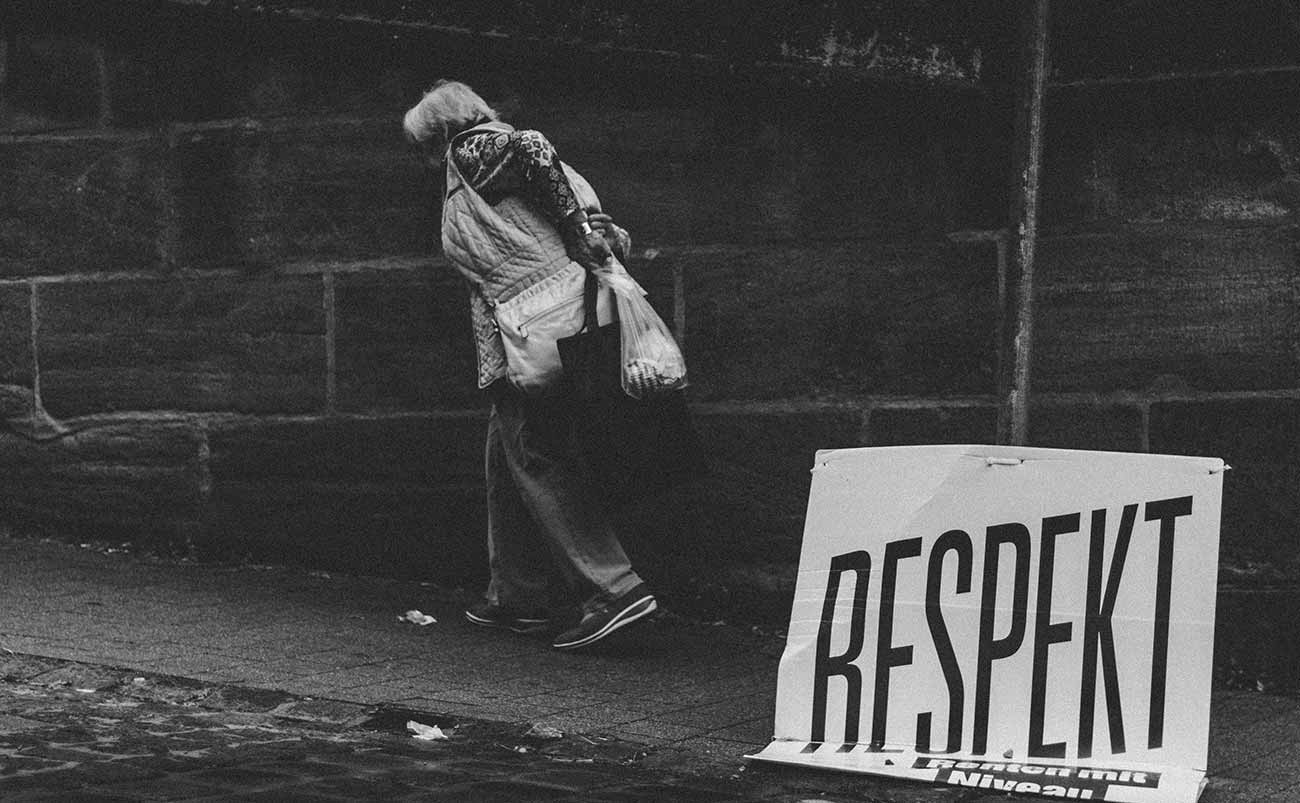 Bild –Eine alte Frau, am Laternenpfosten ein Schild auf dem steht »Respekt –Renten mit Niveau«.