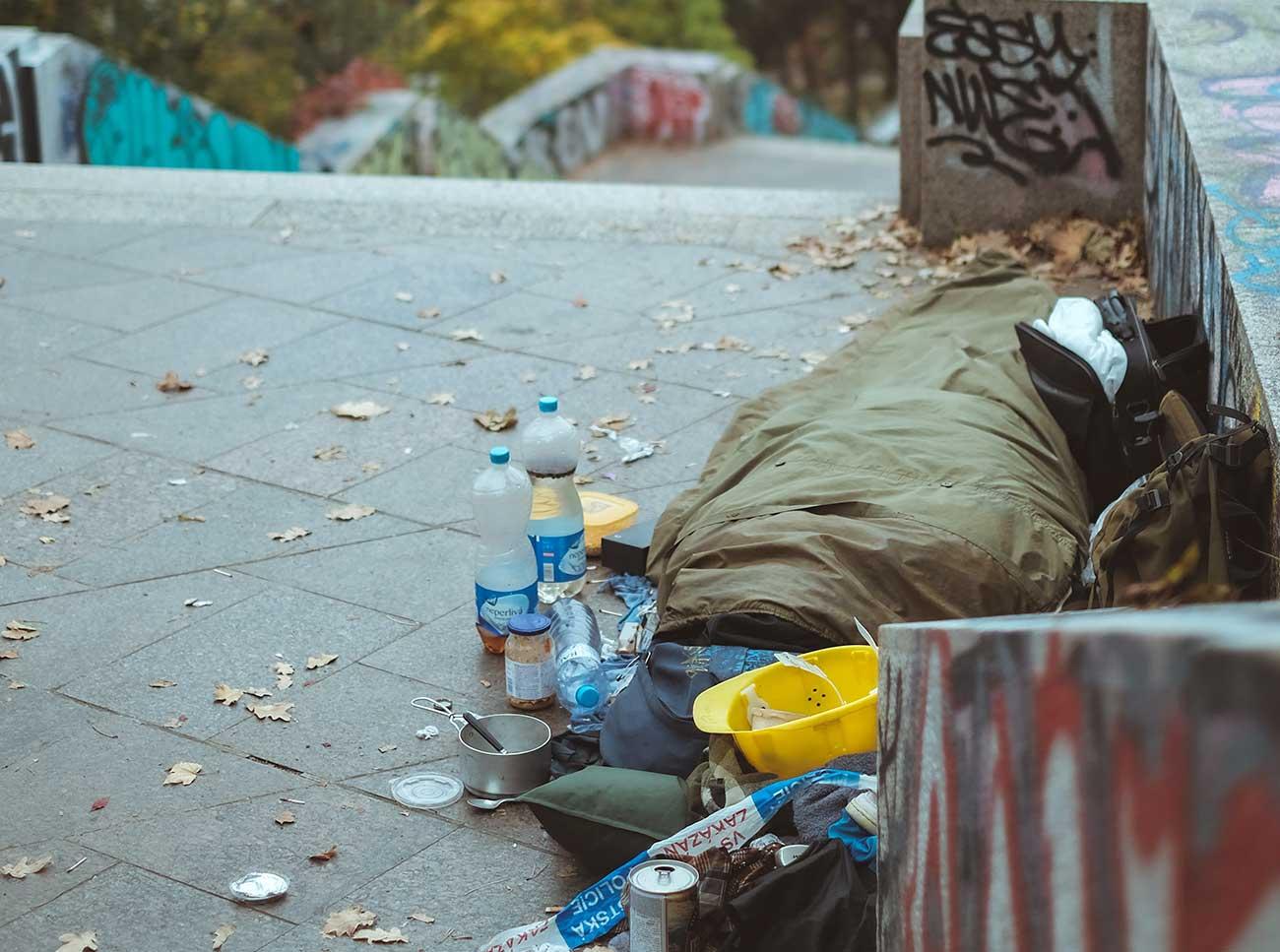 Bild –Eine obdachlose Person im Schlafsack liegend seitlich einer Treppe.