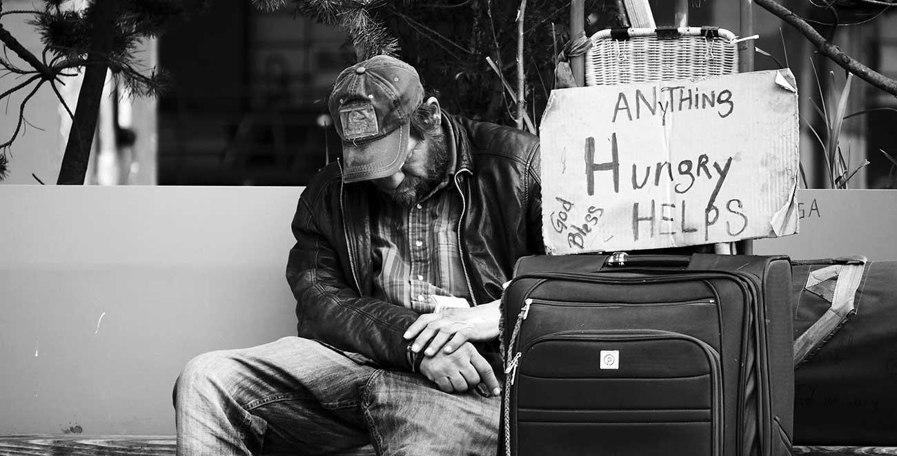 """Bild – Ein obdachloser Mensch, der mit seinem Koffer und einem Schild """"Anything, Hungry, Helps, Good Bless..."""
