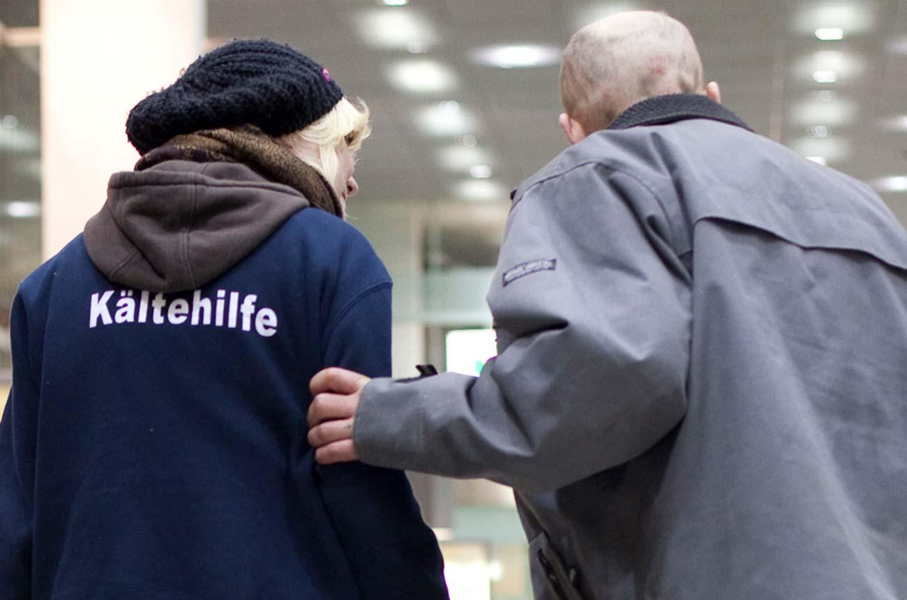 Bild –Frau von der Kältehilfe mit einem alten Mann, der sich an ihr festhält beim Laufen.