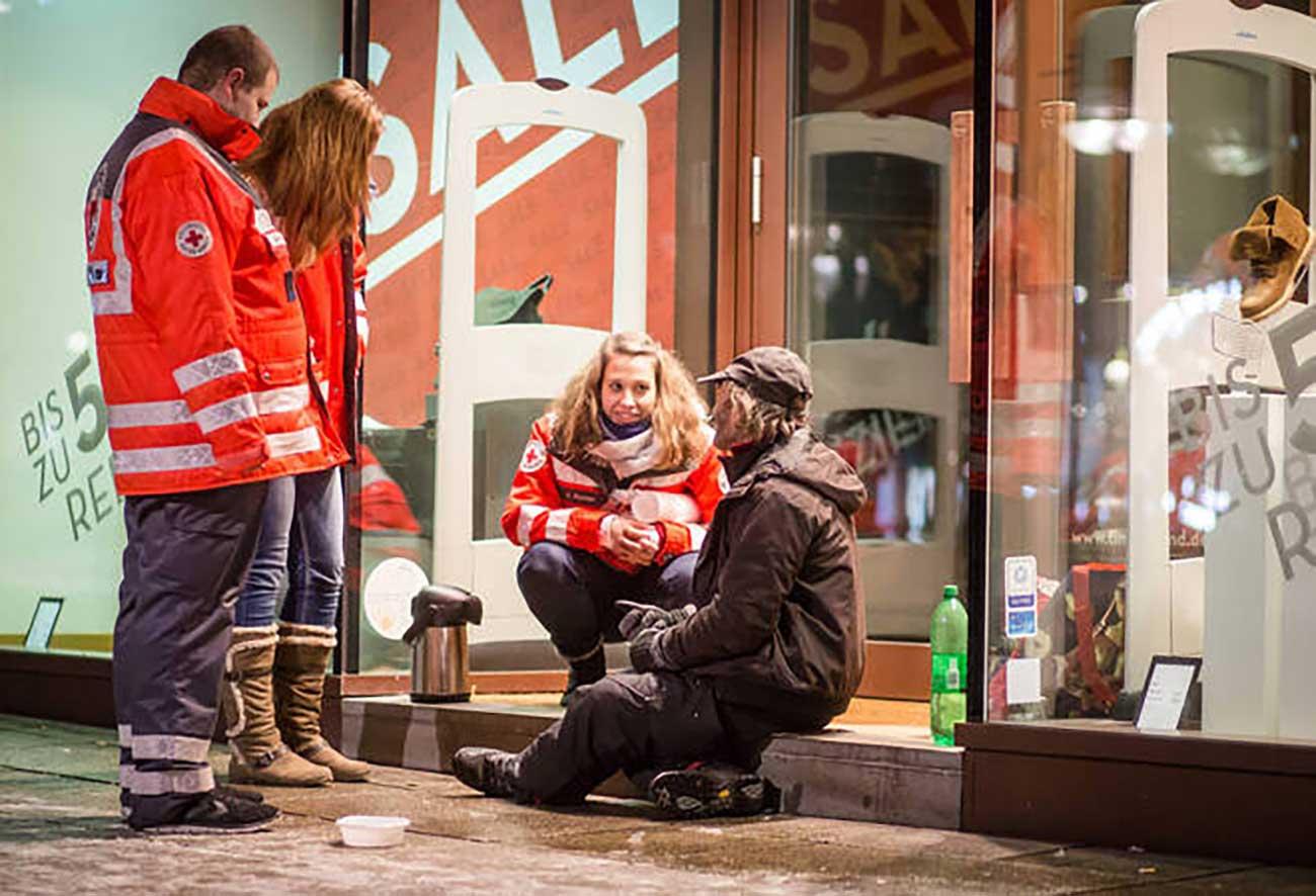 Bild –Drei Mitarbeiter der Kältehilfe im Gespräch mit einem Obdachlosen Menschen, sitzend vor der Eingangstür eines Geschäftes.