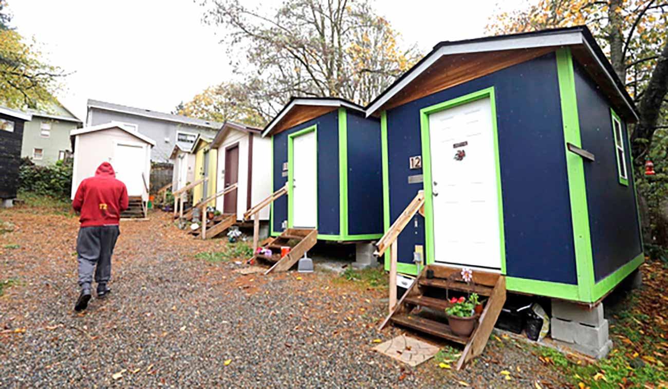 Bild – Eine Reihe von blau-grünen Tiny Houses für Obdachlose.