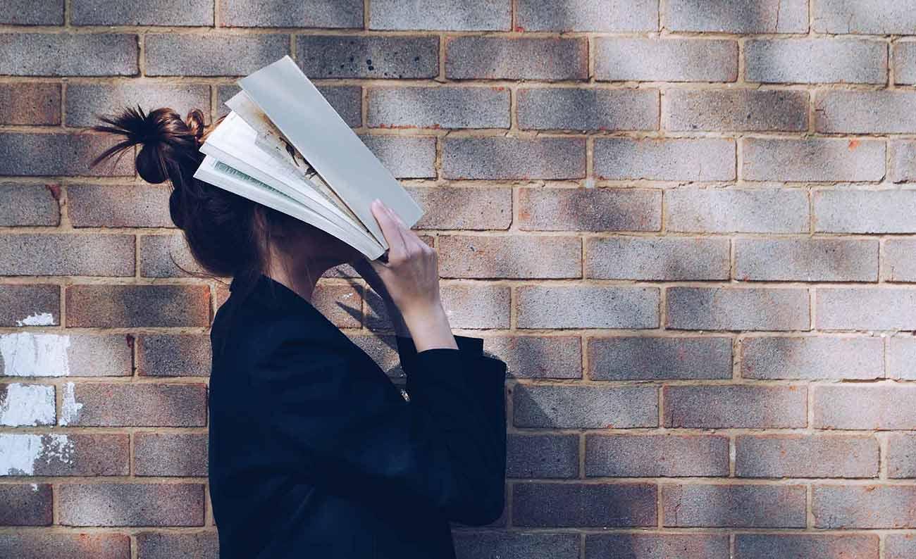 Bild –Eine Frau, die sich ein Magazin seitlich stehend vors Gesicht hält.