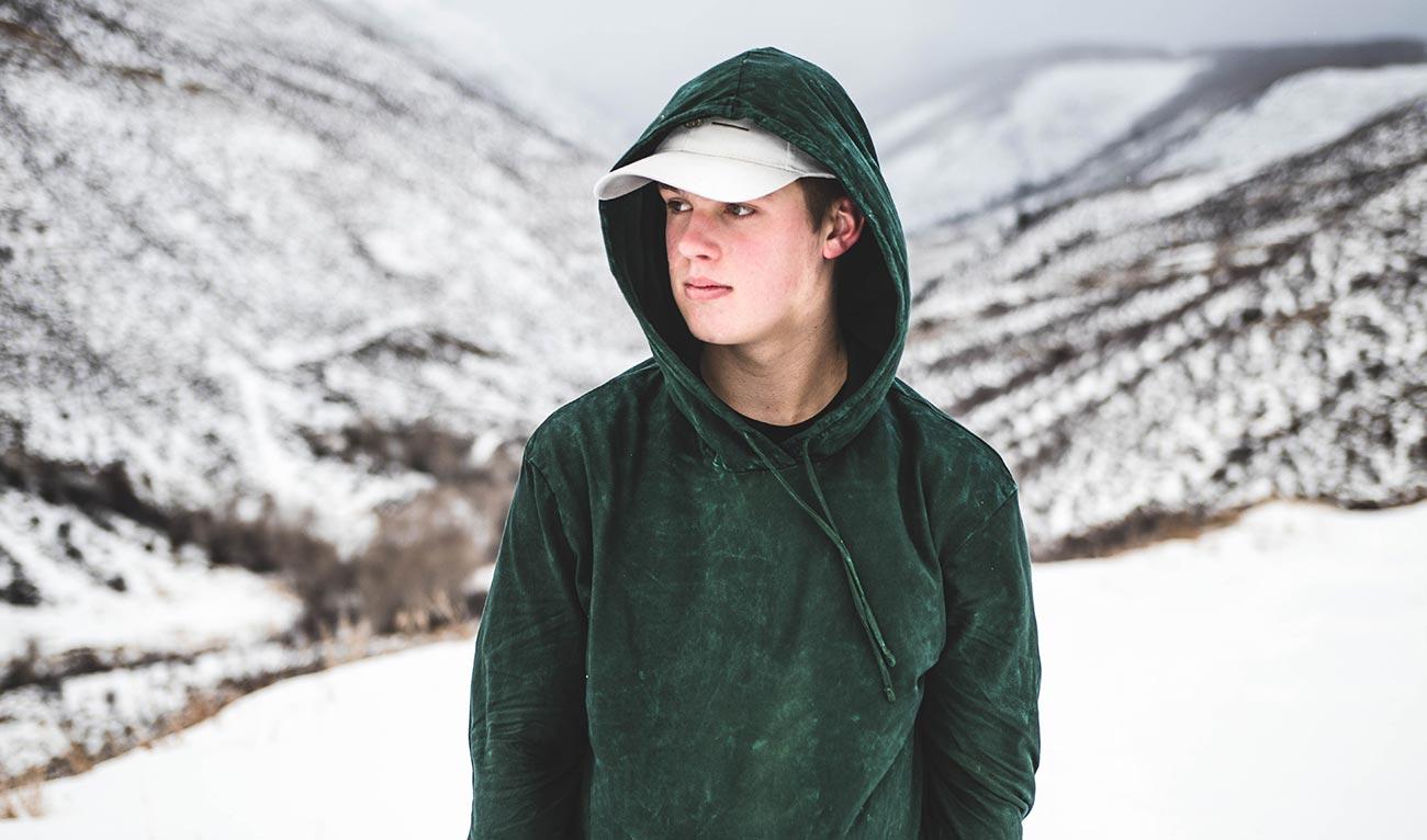 Bild –Junge mit Kapuzenpulli und Schildmütze im Schnee und in den Bergen