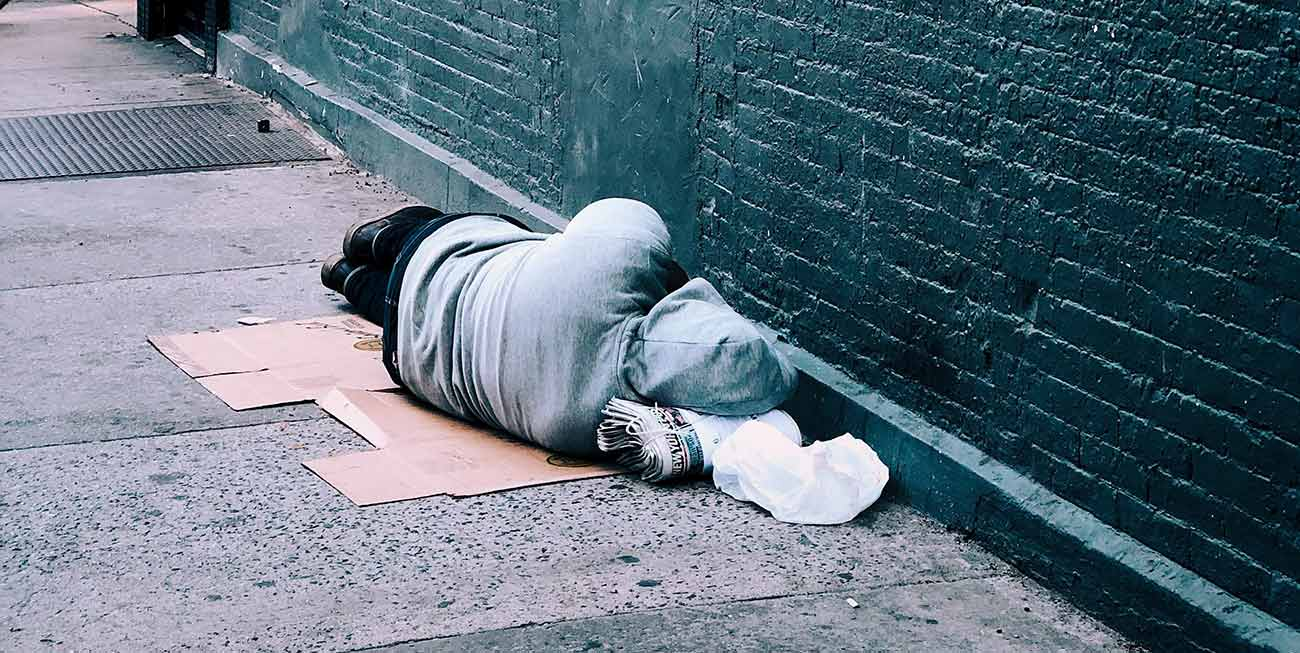 Bild –Eine obdachlose Person auf dem Gehweg liegend.
