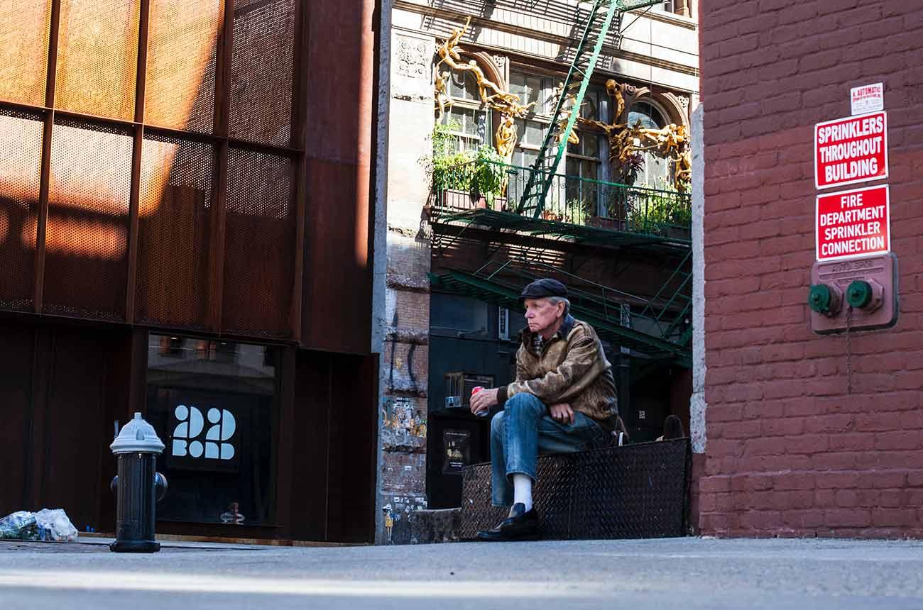 Bild –Alleine sitzender Mann am Straßenrand