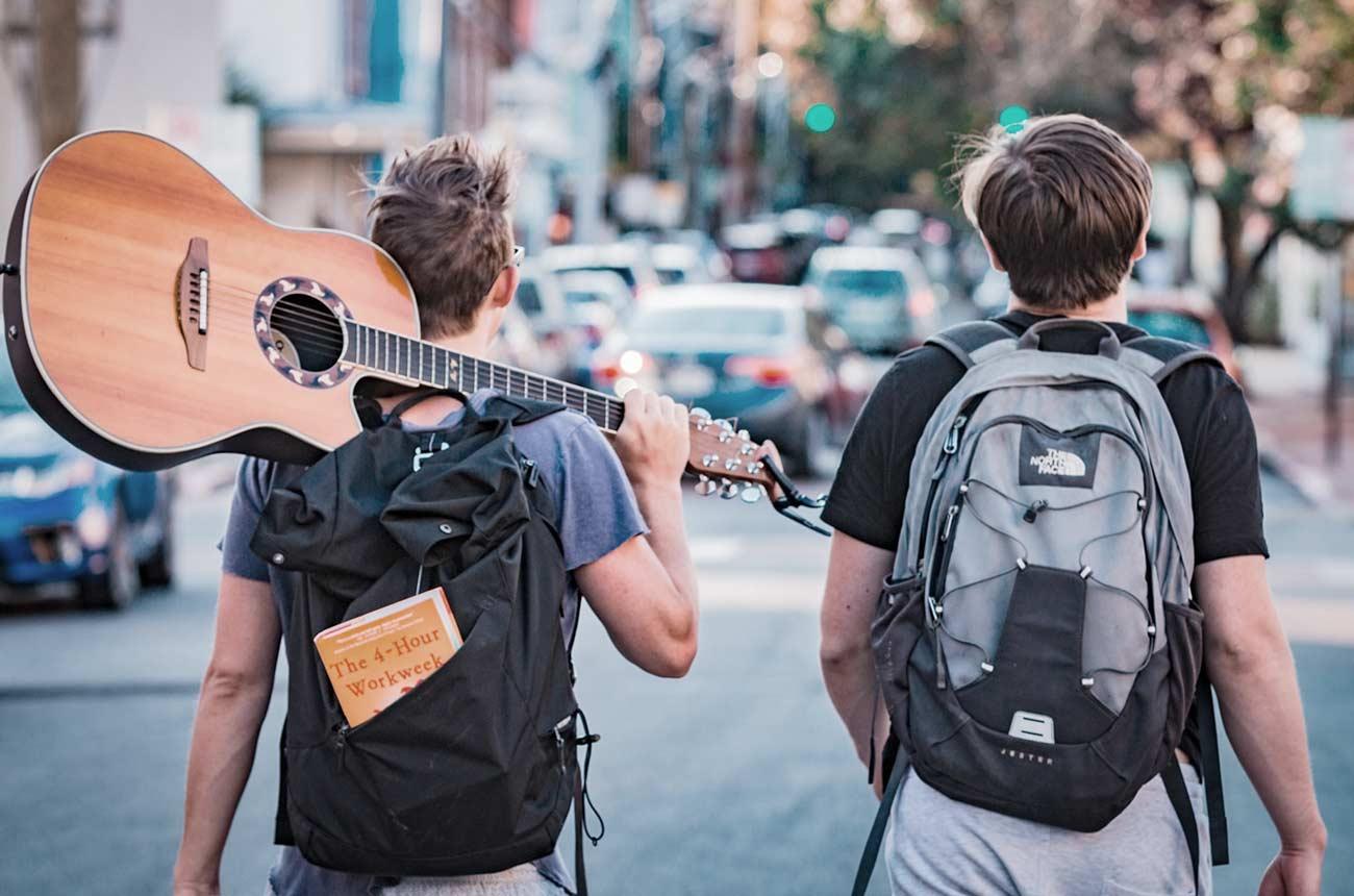 Bild –zwei Jungs mit Rucksack und Gitarre über der Schulter laufend auf der Straße