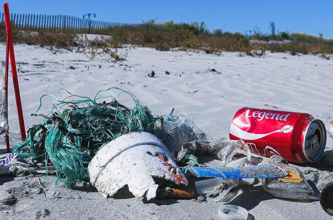 Bild –Plastik, Fischernetz und Coladose am Strand