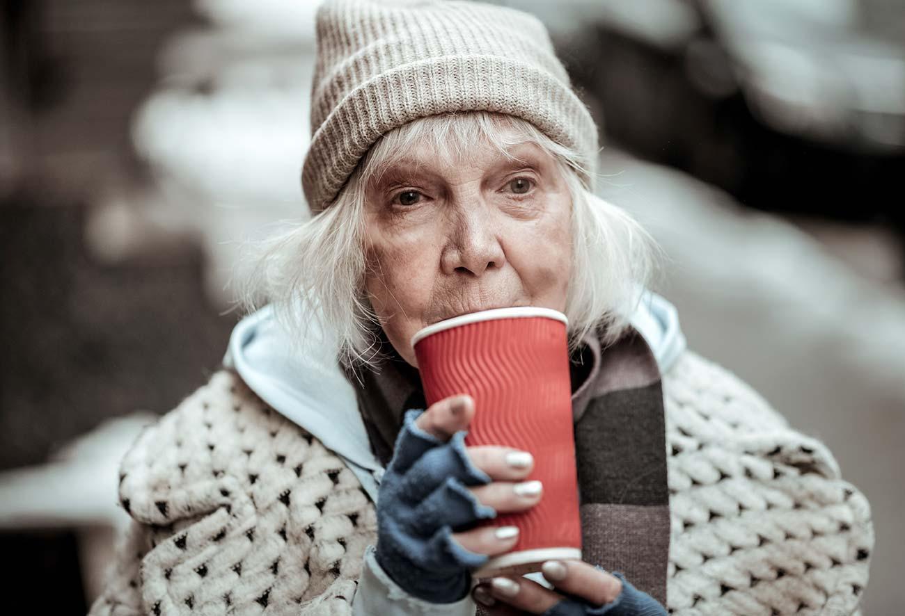 Bild: Thema Kältebus –Alte Dame trinkt ein Warmgetränk