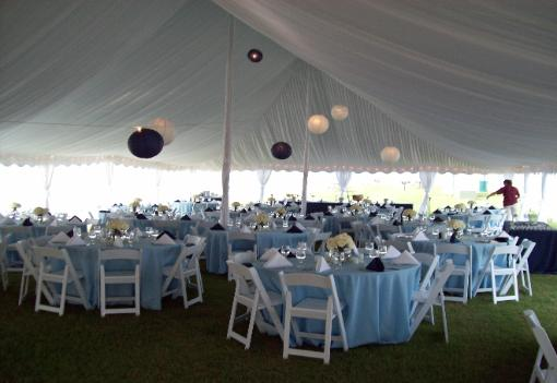 event table display light blue table cloths and white chairs inside a tent