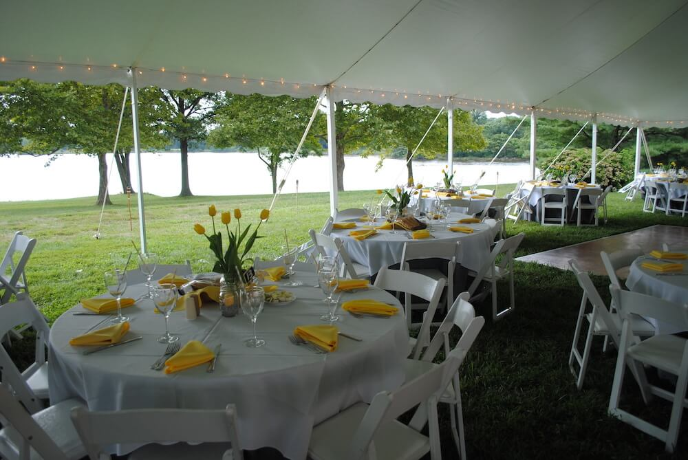 table set outside with white table cloth and yellow napkins