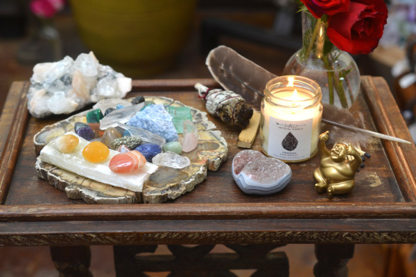 Altar with crystals, candle, roses, and smudge stick