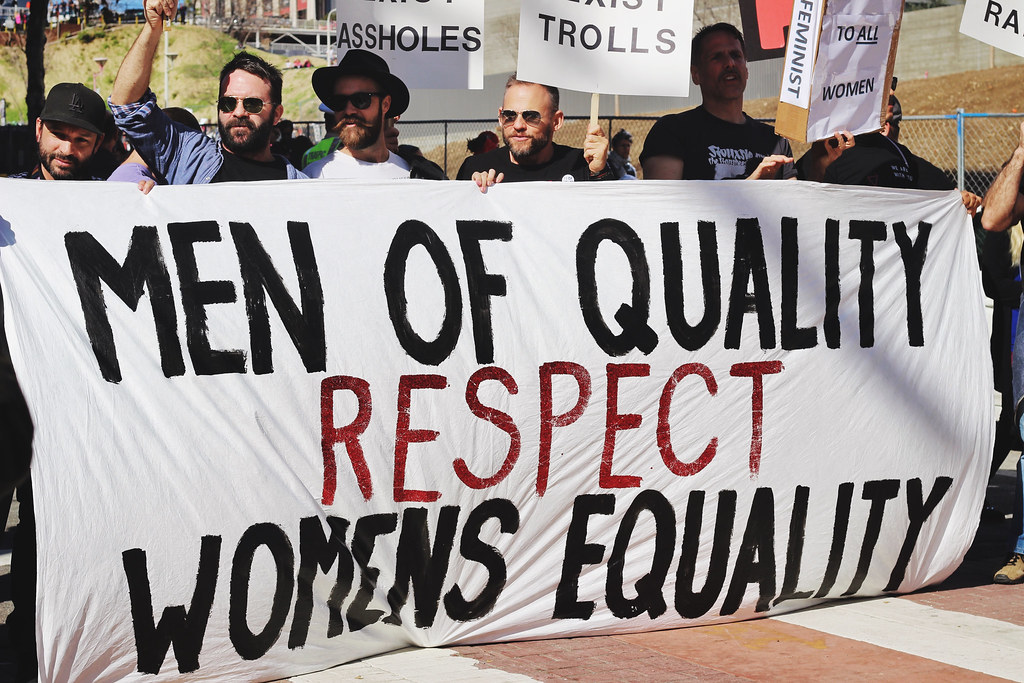 "Men holding a sign that says ""Men of quality respect women's equality"""