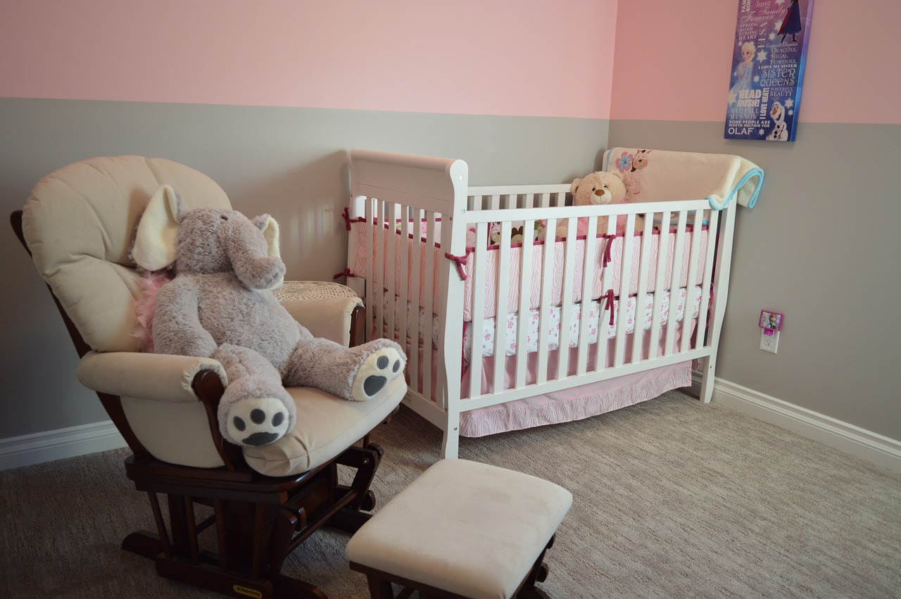 A baby nursery with crib, stuffed animals and a rocking chair