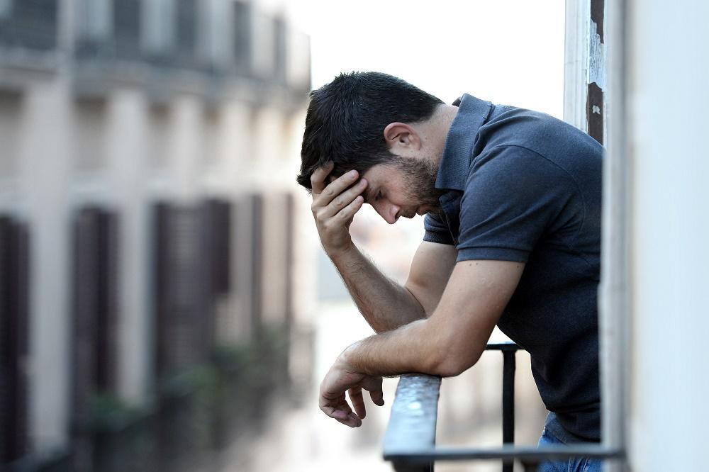 Sad man leaning on balcony