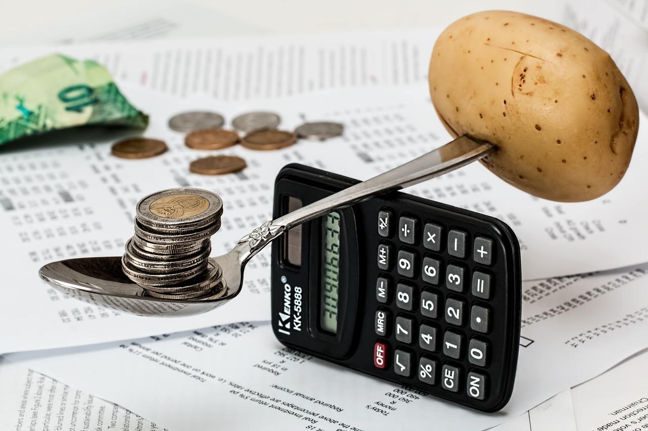A spoon containing coins balances with a potato across a calculator