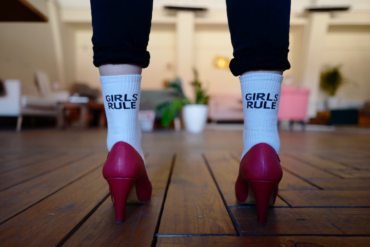Image of person in pink heels with socks that say girls rule.