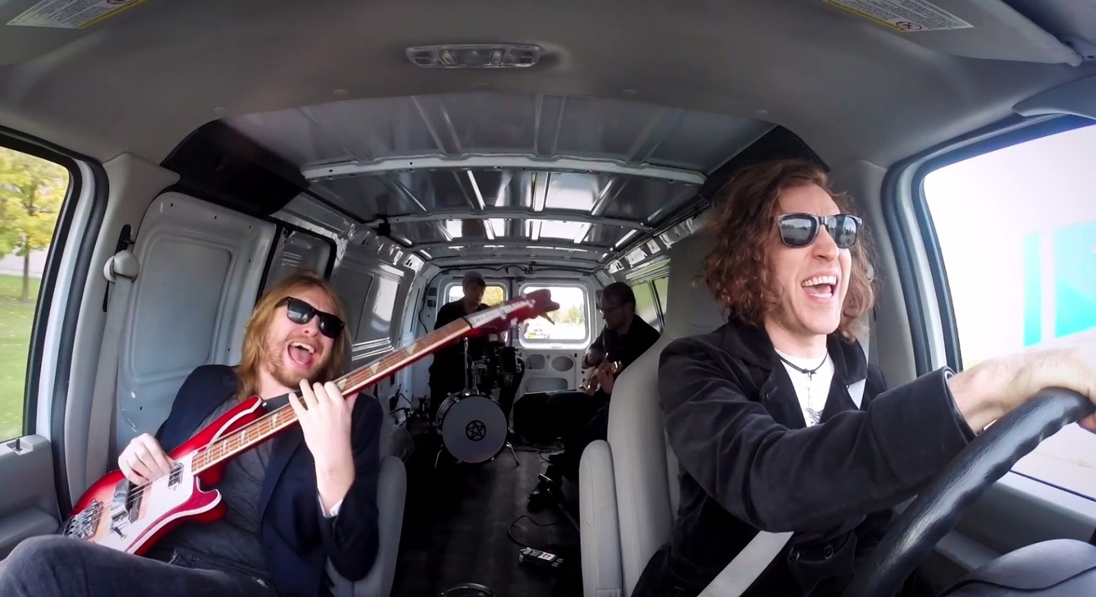A four-piece band driving in a van together. Everyone, except the driver is playing an instrument. In the passenger seat is the bass player, and in the back are the drummer and guitar player.