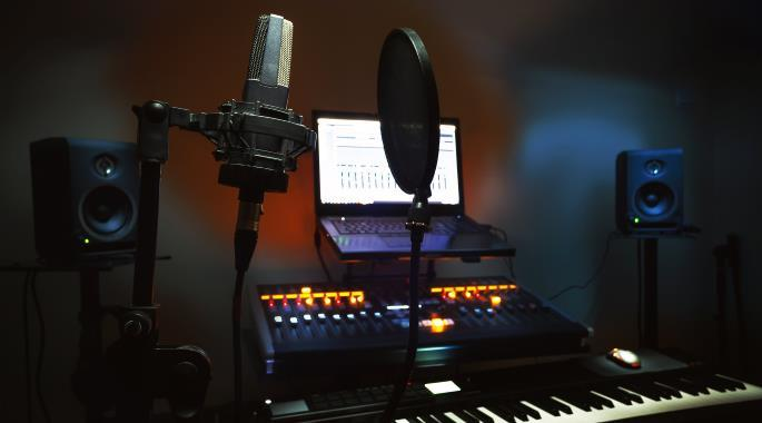 A vocal microphone and pop filter in front of a control desk.