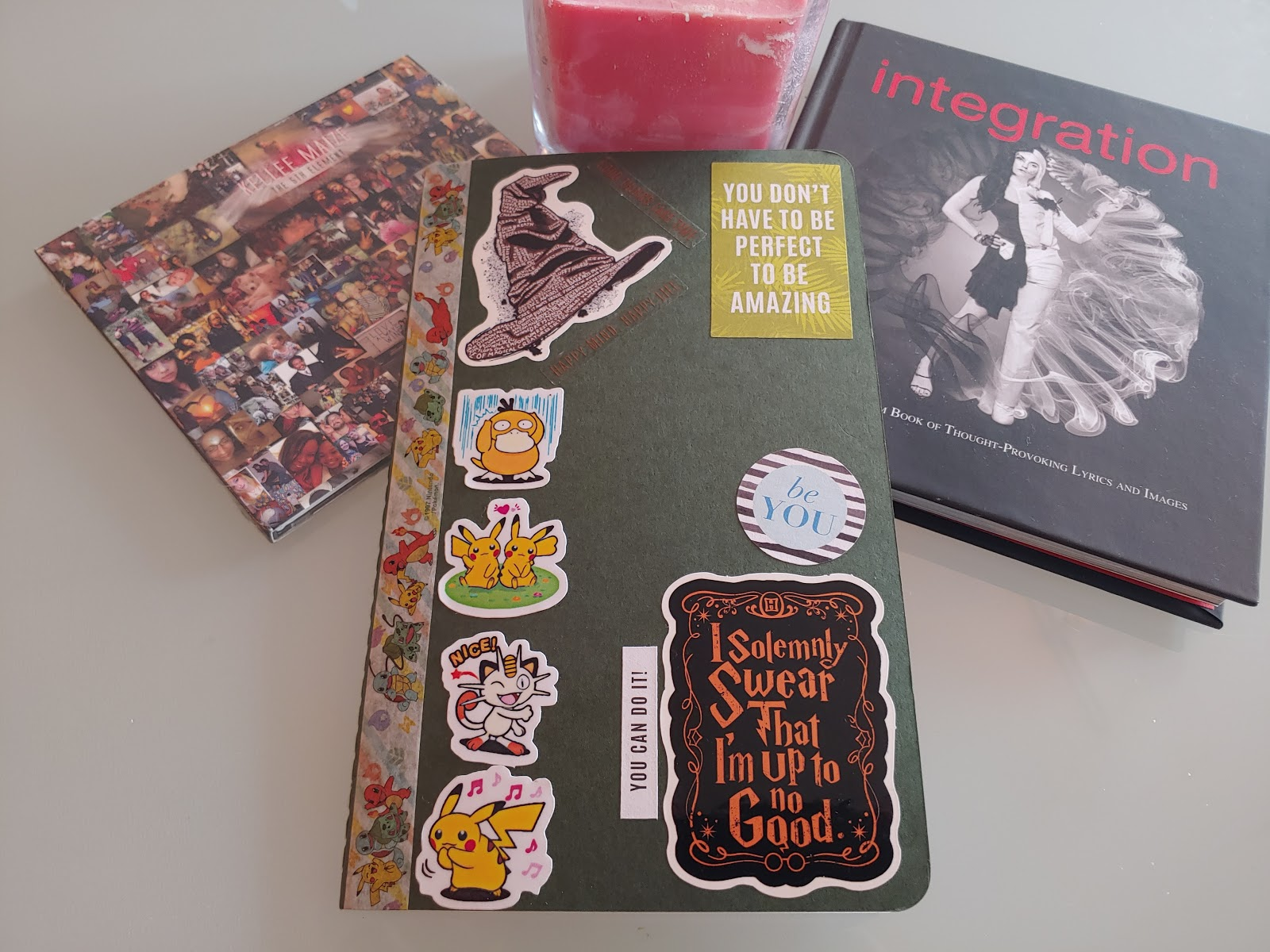 A decorated journal on a table with a book, candle and CD by Kellee Maize