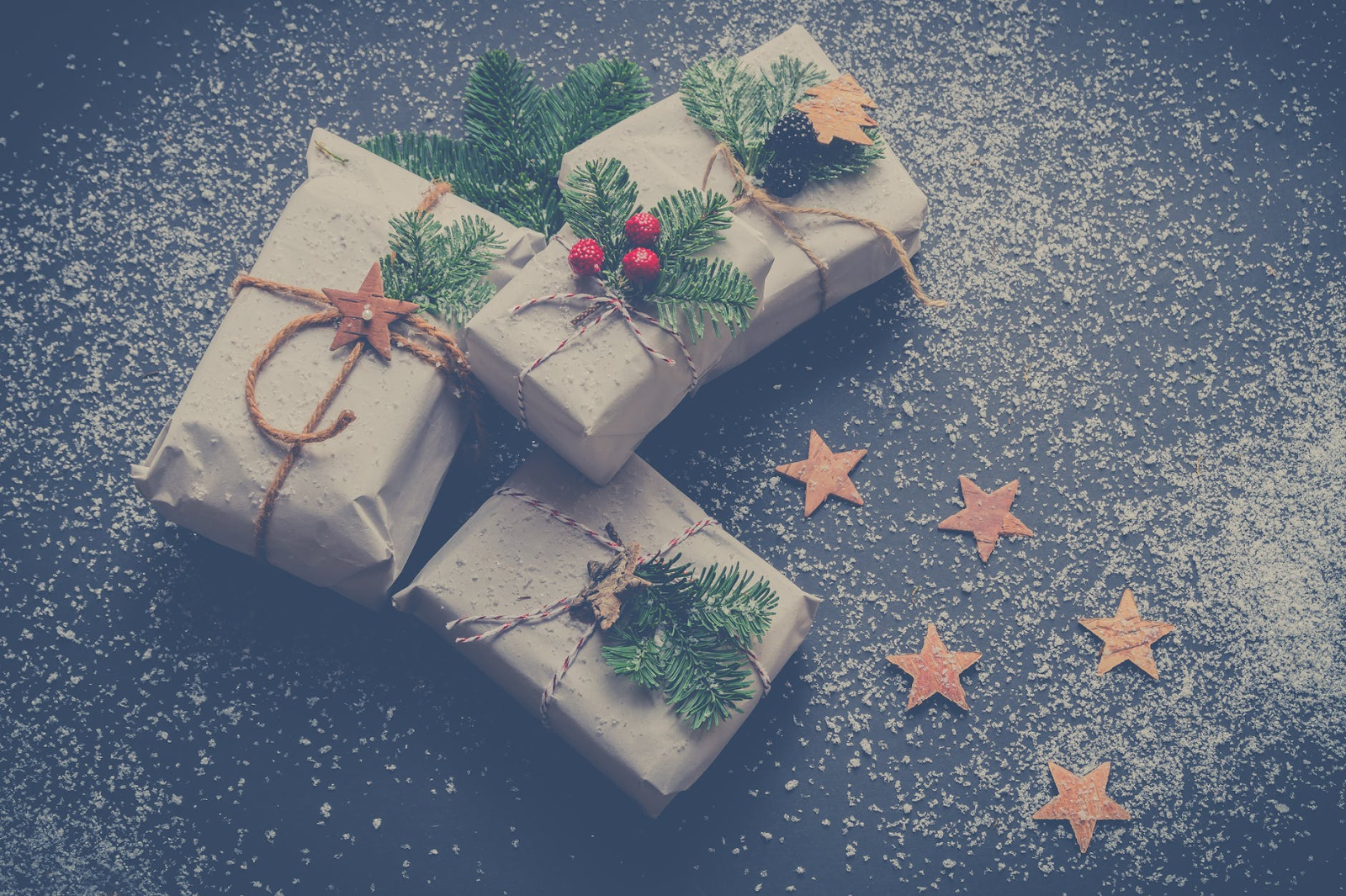 Four presents wrapped in off white paper and tied with twine, evergreen branches and berries against a blue background with snow and cardboard stars.