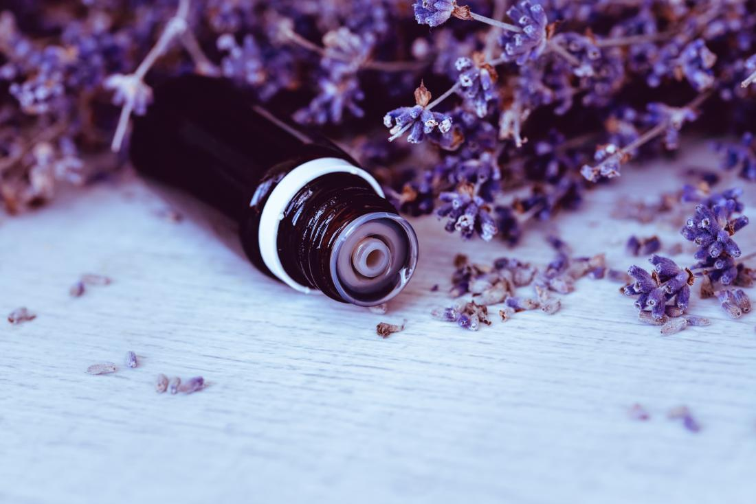 lavender pedals surrounding oil bottle laying down