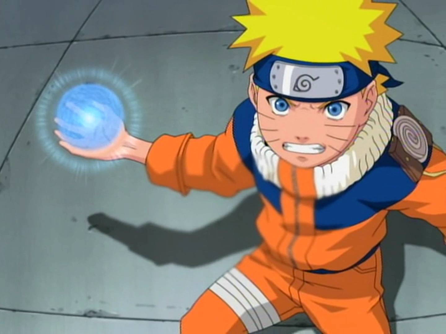 A young boy dressed in an orange and blue jumpsuit holding a blue ball of light in his hand.